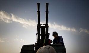 A Libyan rebel fixing an anti-aircraft gun