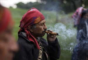 FTA: Jorge Dan Lopez: A man smokes tobacco as an offering during the Day of the Birds ceremony