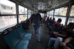 FTA: Jorge Dan Lopez: An armed villager checks a public bus entering their village of Castanas