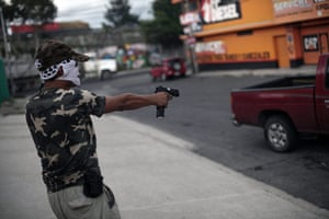 FTA: Jorge Dan Lopez: An armed villager points his gun at a car entering the village of Castanas