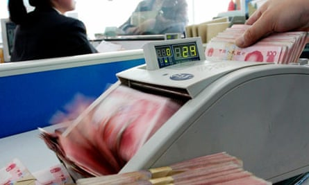 A Chinese bank staff counts renminbi banknotes at a branch of the China Construction Bank in Hai'an