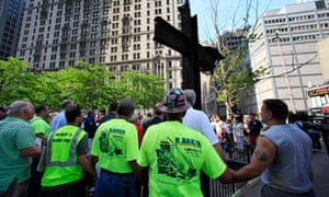 World Trade Centre construction workers hold hands during a prayer at a ceremony for the 9/11 cross