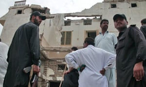 Pakistani security officials inspect the scene of a bomb blast in Balochistan