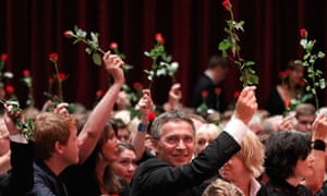 Norway's prime minister, Jens Stoltenberg, holds a red rose during a memorial service