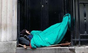 Homeless man sleeps in a doorway in central London