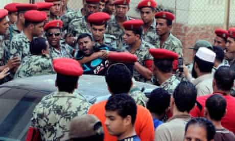 Military police tussle with protesters in Suez