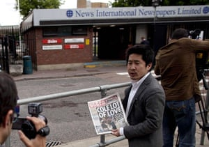 News of The World History: A Japanese journalist holds up a copy the News of the World