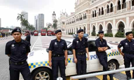 Malaysian police line up near water cannon trucks in a Kuala Lumpur street