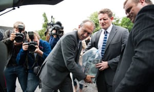 Police officers remove computers and documents from Andy Coulson's home