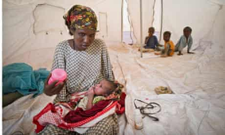 Mother with her new born in new tent in IFO extension, the new camp in Dadaab