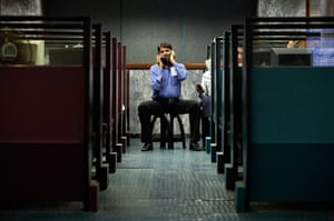 24 hours in pictures: A man uses a phone between booths, Karachi Stock Exchange