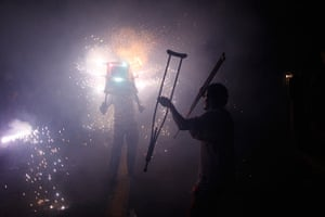 24 hours in pictures: A man lifts his crutches as he watches a fireworks, Santo Domingo