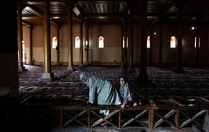 24 hours in pictures: An elderly Kashmiri Muslim woman and a young girl cross a wooden parapet