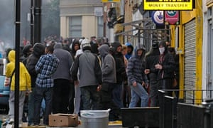 Rioters breaking into a shop in Hackney, north London, on Monday