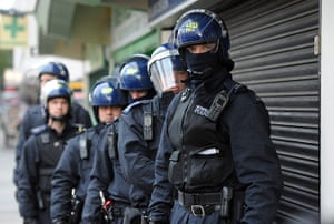 London riots aftermath: Met Police officers prepare to carry out a raid on a property in Pimlico
