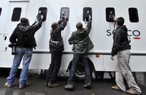 London riots aftermath: Photographers take pictures of a prison van as it leaves court in London