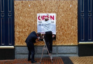London riots aftermath: Workers attach an 'Open for Business' sign to boards on a shop, Birmingham