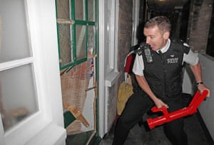 London riots aftermath: Westminster: An officer enters a property as police recover stolen goods