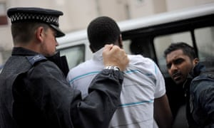 A man is led away yesterday after a police raid in Pimlico, central London