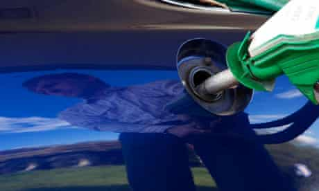 A motorist uses a petrol pump at a petrol station
