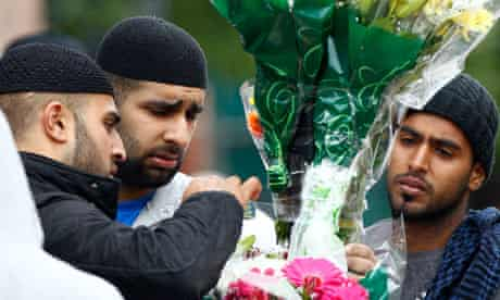 Locals place flowers at the scene where three men were killed in the Winson Green area of Birmingham