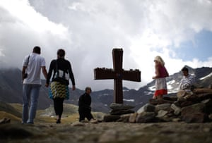 24 hours in pictures: Austria: Tourists walk next to the cross on the Timmelsjoch mountain