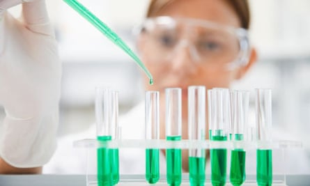 Scientist filling test tubes with pipette in laboratory