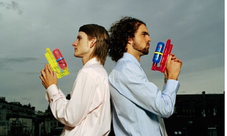 Two men standing back to back holding water pistols