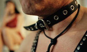 Man wearing leather collar and harness.