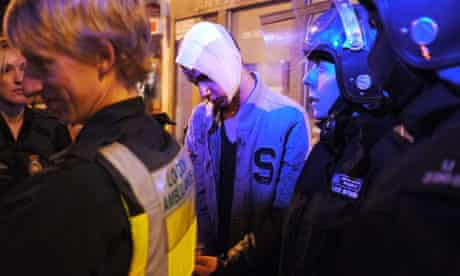 An injured man in handcuffs at the scene of looting