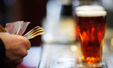 Customer pays for a Fosters beer at the Occidental Hotel in central Sydney