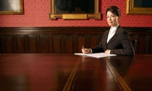 A woman sits alone in a boardroom