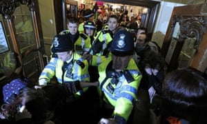 Police officers try to stop protesters occupying Fortnum & Mason