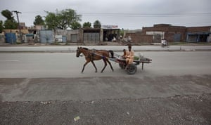 FTA: Adrees Latif   : A man and boy ride a horse and cart past the same location in Nowshera