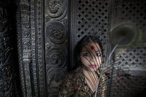 24 hours in pictures: Lalitpur, Nepal: A girl holds a peacock feather during a festival