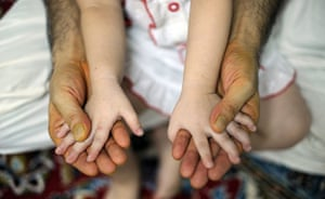 24 hours in pictures: Kuala Lumpur, Malaysia: An Afghan migrant holds the hands of his daughter