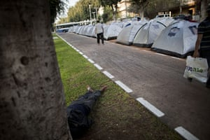 FTA: Oded Balilty: An Israeli man walks past tents as another man rests underneath a tree