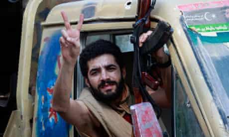 A Libyan rebel fighter celebrates as he drives through Tripoli