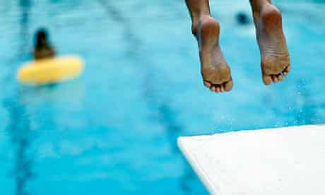 A boy jumps off a diving board into a swimming pool