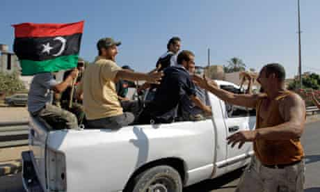 Local residents greet advancing rebel fighters on the outskirts of Tripoli, Libya.