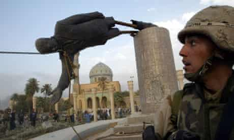 A US soldier watches as the statue of Iraq's Saddam Hussein falls
