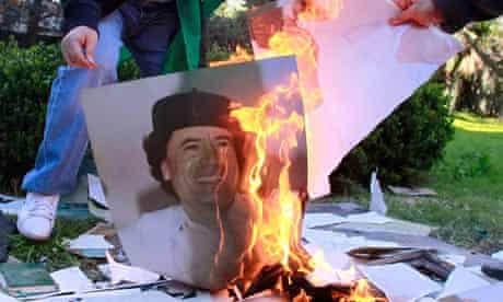 Employees of the Libyan Embassy burn a portrait of Gaddafi in Buenos Aires