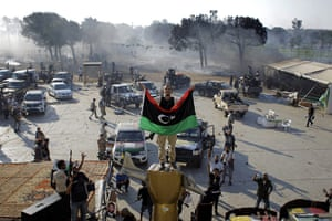 Gaddafi's compound falls: A rebel fighter gestrures as he stands on the monument inside the compound