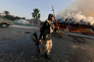 Gaddafi's compound falls: A rebel fighter displays a looted golden gun from the compound