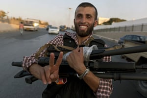 Gaddafi's compound falls: A rebel fighter with guns taken from the compound