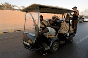 Gaddafi's compound falls: Rebel fighters ride in a golf buggy taken from Gaddafi's headquarters