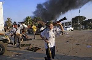Gaddafi's compound falls: A rebel fighter carry a  gun inside the main Muammar Gaddafi compound