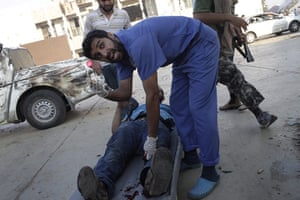 Gaddafi's compound falls: A doctor rescues a wounded rebel during the battle for the compound
