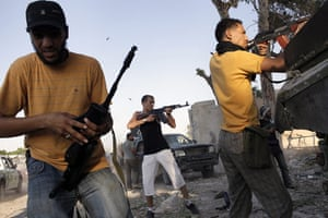 Gaddafi's compound falls: Libyan rebels shoot at Gaddafi supporters during the battle for compound