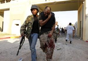 Gaddafi's compound falls: A Libyan rebel assists an injured fellow rebel
